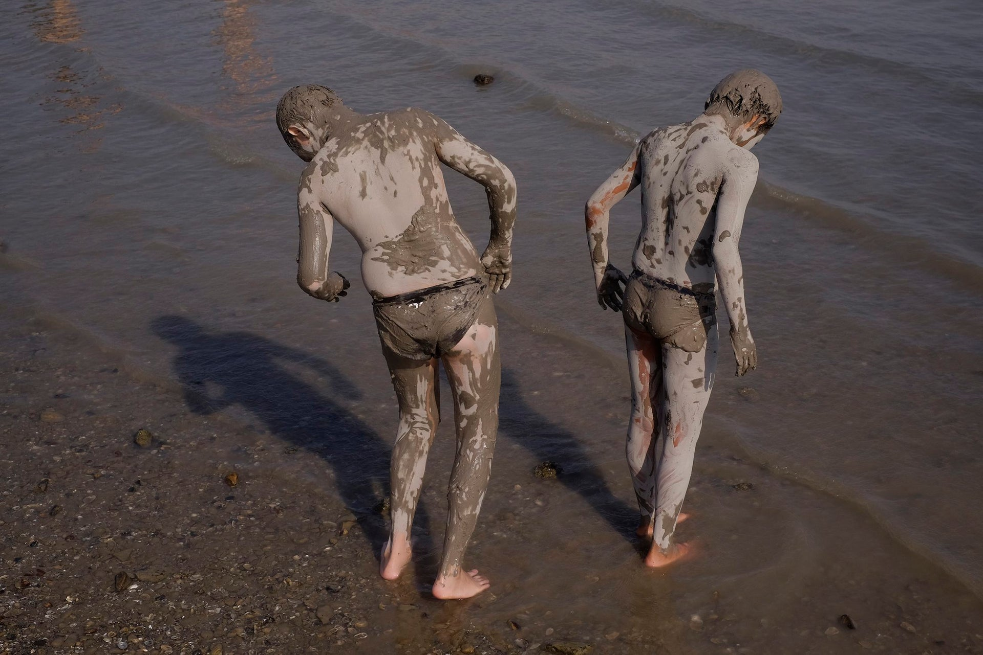 Two Israeli youth covered with mud during the annual Sea of Galilee swim, the oldest and largest popular swimming event, near Tiberias, northern Israel, Saturday, Sept. 16, 2017.