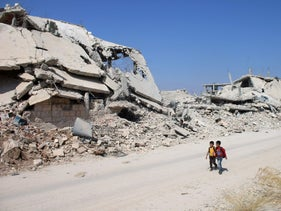 Syrian schoolchildren walk past destroyed buildings in a rebel-held area of Daraa, September 17, 2017.