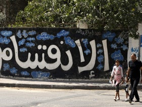 "A Palestinian man and his daughter walk past the Arabic word ""division"" painted on a wall in Gaza City, on September 17, 2017."