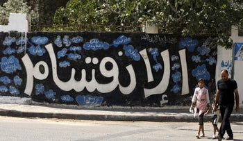 """A Palestinian man and his daughter walk past the Arabic word """"division"""" painted on a wall in Gaza City, on September 17, 2017."""