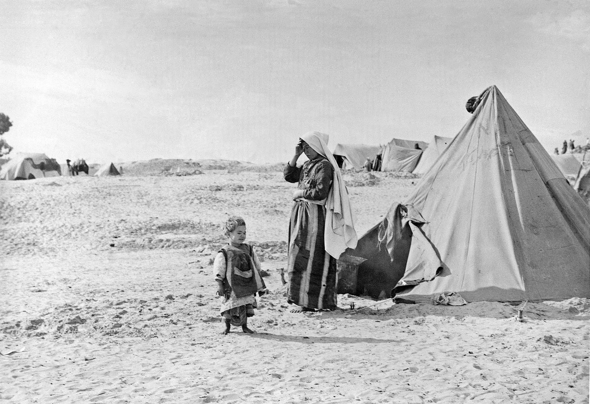 In this 1948 photo from the UN Relief and Works Agency, UNRWA, archive, Palestinian refugees stand outside their tent in Khan Younis, Gaza Strip.
