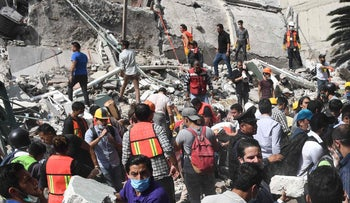 Rescuers and volunteers clear the rubble in search of survivors amid the ruins of a collapsed building after a powerful quake in Mexico City on September 19, 2017.
