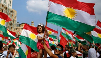 A man holds a girl waving a Kurdish flag as they gather to support the Kurdish referendum in Iraq, at Martyrs Square in Downtown Beirut, Lebanon, September 17, 2017.