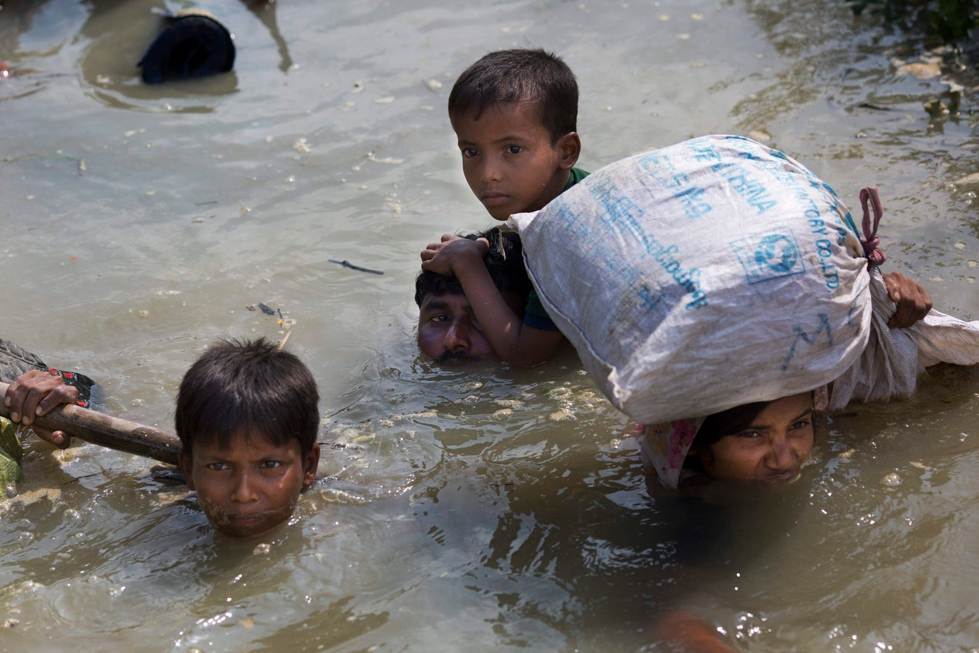 In this Sept. 5, 2017, file photo, young Rohingya boys with their family reach the Bangladesh border after crossing a creek of the Naf River on the border with Myanmar, in Cox's Bazar's Teknaf area.