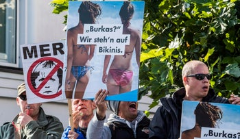"Members of the Alternative for Germany party display placards reading, ""Burkas? We prefer prefer bikinis"" as Angela Merkel arrived for a rally in Binz, September 16, 2017."