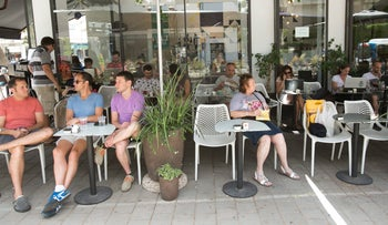 Patrons sit at a cafe in Tel Aviv, June 5, 2016.