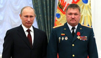 FILE PHOTO: Valery Asapov, right, who was killed in Syria, poses for a photo with Russian President Vladimir Putin, during an award ceremony in the Kremlin in Moscow, Russia in 2013.
