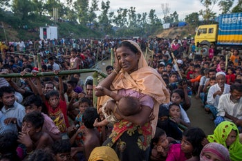 A Rohingya Muslim woman, who crossed over from Myanmar into Bangladesh, wipes her sweat as she waits to receive aid near Balukhali refugee camp, Bangladesh, September 25, 2017.