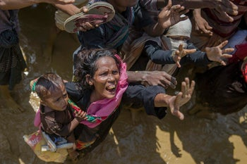 A Rohingya Muslim women, who crossed over from Myanmar into Bangladesh, holds a child as she shouts at volunteers distributing aid to hand her a bag of rice near Balukhali refugee camp, Bangladesh, Thursday, Sept. 21, 2017