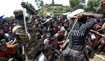 Military and local security personnel keep Rohingya refugees in line as they queue for aid at Cox's Bazar, Bangladesh, September 26, 2017.