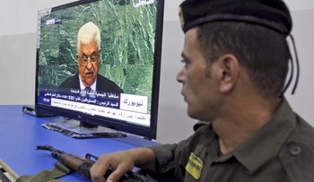"""A Palestinian security officer, loyal to Palestinian president Mahmoud Abbas, watches a television screen showing Palestinian President Mahmoud Abbas address the 67th session of the United Nations General Assembly at U.N. headquarters , in the West Bank city of Jenin, Thursday, Sept. 27, 2012. Palestinian President Mahmoud Abbas accused Israel of ethnic cleansing Thursday for building settlements in east Jerusalem.""""It is a campaign of ethnic cleansing against the Palestinian people via the demolition of their homes,"""" Abbas said in his speech to the U.N. General Assembly. (AP Photo/Mohammed Ballas)"""