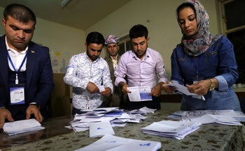 Kurdish officials count votes after the close of polls during the referendum on independence at a polling station in Arbil, the capital of the autonomous Kurdish region of northern Iraq, on September 25, 2017.