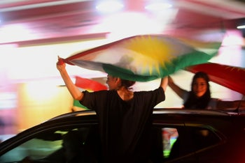 Syrian Kurds wave the Kurdish flag as they celebrate in the northeastern Syrian city of Qamishli on September 25, 2017, in support of the independence referendum in Iraq's autonomous northern Kurdishregion.