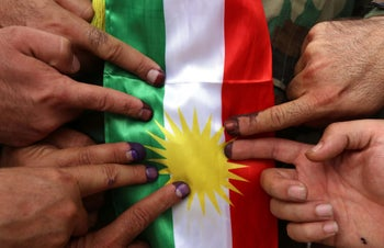 Members of a Kurdish Peshmerga battalion show their ink-stained fingers after voting in the Kurdish independence referendum in Arbil. September 25, 2017