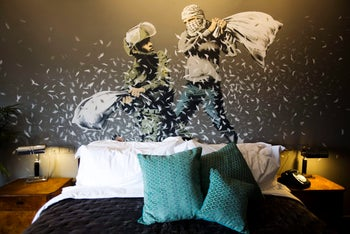 "A Banksy wall painting showing Israeli border policeman and Palestinian in a pillow fight in a room in  the ""The Walled Off Hotel"", Bethlehem. March 3, 2017"