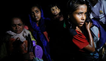 Women carry children through the water as hundreds of Rohingya refugees arrive under the cover of darkness by wooden boats from Myanmar to Bangladesh, September 27, 2017.
