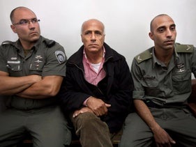 File photo: Israeli nuclear whistleblower Mordechai Vanunu sits between two prison guards as he waits in a courtroom before a hearing in Jerusalem, December 2009.