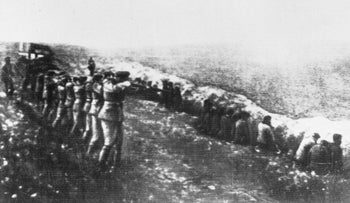 A Nazi firing squad shooting Soviet civilians in the back as they sit beside their own mass grave, in Babi Yar, Kiev.
