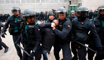 People clash with Spanish Guardia Civil guards outside a polling station for 2017 referendum on independence for Catalonia the in Sant Julia de Ramis on October 1, 2017.