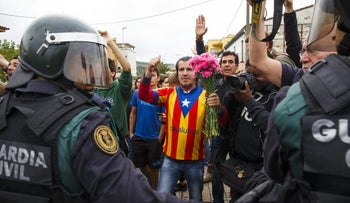 Civil Guard officers face a man wearing a pro-independence Catalan shirt outside a polling station,  Sant Julia de Ramis, Spain, October 1, 2017.