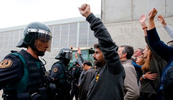 People clash with Spanish Guardia Civil guards outside a polling station in Catalonia