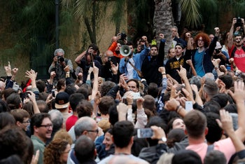 People react as they listen a speech at a courtyard outside a polling station for the banned independence referendum in Barcelona, Spain, October 1, 2017.