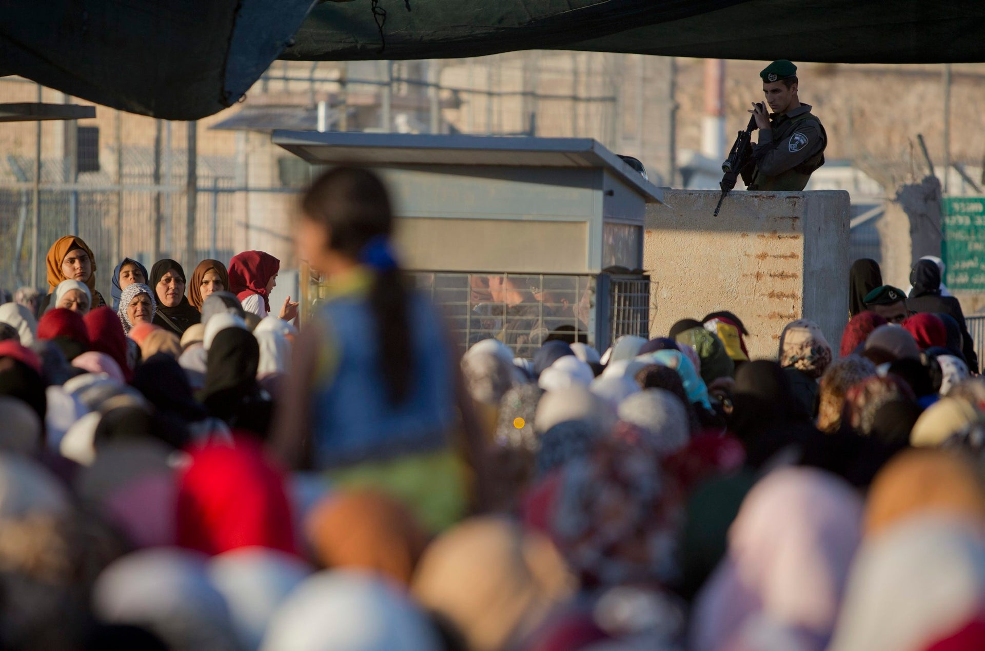 An Israeli border police officer stands as Palestinian women wait to cross the Qalandiyah checkpoint between the West Bank city of Ramallah and Jerusalem on their way to pray at Al-Aqsa Mosque during Ramadan, Friday, June 17, 2015.