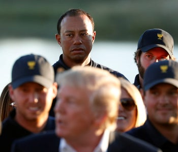 Tiger Woods watches as U.S. President Donald Trump congratulates players before presenting the trophy to the U.S. team at the conclusion of the Presidents Cup golf tournament at Liberty National Golf Club in Jersey City, New Jersey, U.S., October 1, 2017. REUTERS/Kevin Lamarque