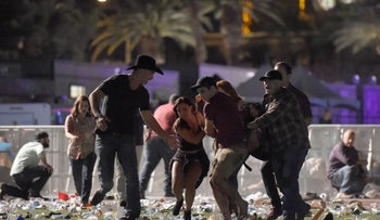 People carry a person after apparent gunfire was heard on October 1, 2017 in Las Vegas, Nevada