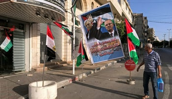 A man looks at a poster depicting Palestinian President Mahmoud Abbas and Prime Minister Rami Hamdallah in Gaza City on October 1, 2017.