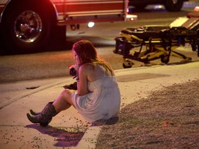 A woman sits on a curb at the scene of a shooting outside of a music festival in Las Vegas, Nevada, October 2, 2017.