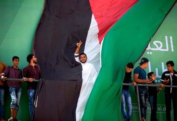 A Palestinian man flashes the sign for victory at the Erez crossing in the northern Gaza Strip for the arrival of Palestinian prime minister Rami Hamdallah and his government on October 2, 2017