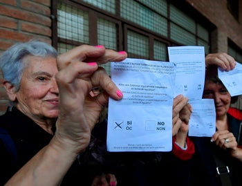 Woman hold ballots at a polling station in Sant Julia de Ramis, where Catalan president is supposed to vote, on October 1, 2017, on the day of a referendum on independence for Catalonia banned by Madrid.