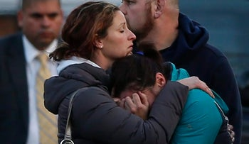 File photo: The families of victims grieve near Sandy Hook Elementary School, were a gunman opened fire on school children and staff in Newtown, Connecticut on December 14, 2012.