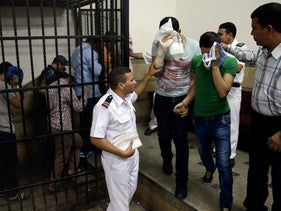 """File photo: Egyptian men convicted for """"inciting debauchery"""" in 2014 leave the defendant's cage in Cairo, Egypt."""