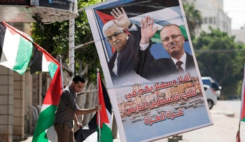 A shop owner displays national flags and a poster bearing the portraits Palestinian Prime Minister Rami Hamdallah and President Mahmoud Abbas, Gaza City, October 1, 2017.