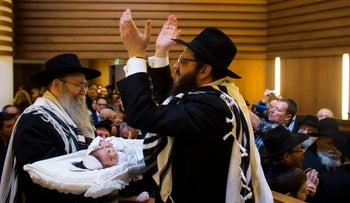 A rabbi cheers as another rabbi holds his son during the circumcision ceremony at the Chabad Lubawitsch Orthodox Jewish synagogue in Berlin, Germany, March 3, 2013.