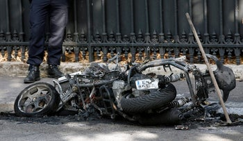 A police officer stands next to a burnt scooter outside the office of Jordan's military attache in Paris, Wednesday, Oct. 4, 2017. A police official told The Associated Press that the scooter caught fire Wednesday morning and caused a small explosion. The fire caused damage to a diplomatic vehicle and was extinguished. (AP Photo/Thibault Camus)