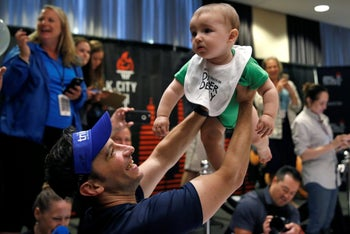 """A father holds up his baby after competing in a """"Diaper Derby"""" crawling race in New York, July 14, 2017."""