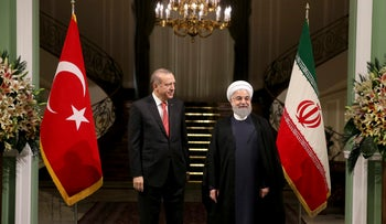 Turkish President Recep Tayyip Erdogan, left, is welcomed by Iranian President Hassan Rouhani, right, during an official arrival ceremony at the Saadabad Palace in Tehran, Iran, Wednesday, Oct. 4, 2017.