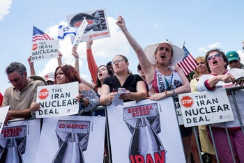 Attendees hold signs and cheer during a Tea Party Patriots rally against the Iran nuclear deal on Capitol Hill in Washington, September 9, 2015.
