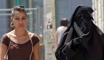 Two women, one wearing the niqab, a veil worn by the most conservative Muslims that exposes only a woman's eyes, right, walk side by side, Marseille, France.