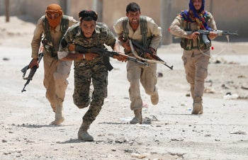 Kurdish fighters from the People's Protection Units (YPG) run across a street in Raqqa, Syria July 3, 2017.