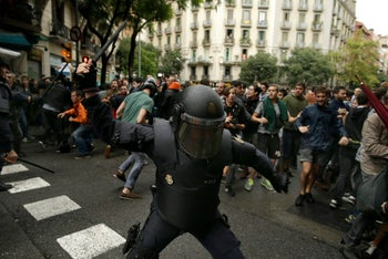 A Spanish riot policeman swings a club against would-be voters near a Barcelona polling station. Oct. 1, 2017
