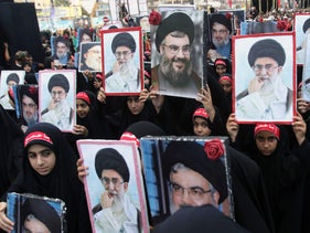 Children of Hezbollah members hold portraits of Hezbollah chief Hasan Nasrallah and Iran's supreme leader Ayatollah Ali Khamenei, October 4, 2017.