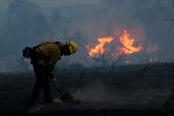 A firefighter works to put out hot spots on a fast moving wind driven wildfire in Orange, California on October 9, 2017.