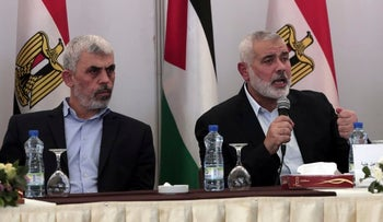 Hamas leader in the Gaza Strip Yahya Sinwar, left, and Palestinian Prime Minister Rami Hamdallah, right, listen to head of the Hamas political bureau Ismail Haniyeh, speech during a meeting in Gaza City, Tuesday, Oct. 3, 2017.(AP Photo/ Khalil Hamra)