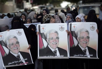 Women demonstrate with posters of Palestinian President Mahmoud Abbas in Gaza City, October 3, 2017.