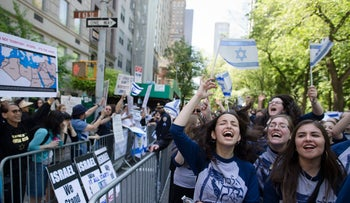 Marchers cheer as they pass along a barricade separating them from anti-Boycott, Divestment and Sanctions (BDS) movement protestors during the Celebrate Israel Parade, Sunday, June 1, 2014, in New York. Among the 35,000 marchers were New York Gov. Andrew Cuomo, New York City Mayor Bill de Blasio, Israeli diplomats and members of the Knesset, Israel's parliament.