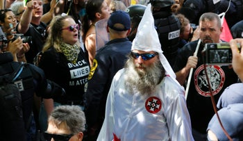 File photo: Members of the KKK escorted by police past a large group of protesters during a KKK rally in Charlottesville, Va., July 8, 2017.